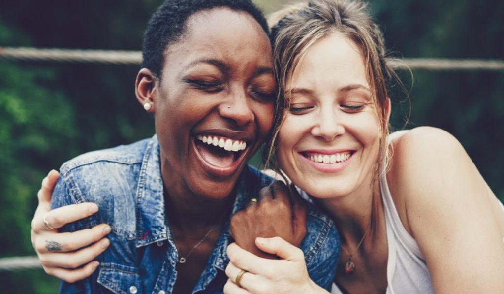 zwei frauen lachen und umarmen sich
