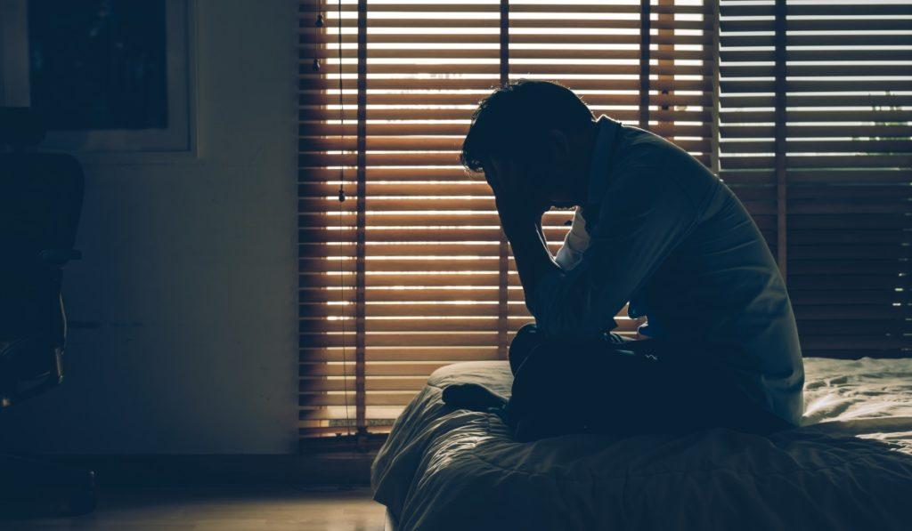 Mann sitzt traurig im dunklen Schlafzimmer