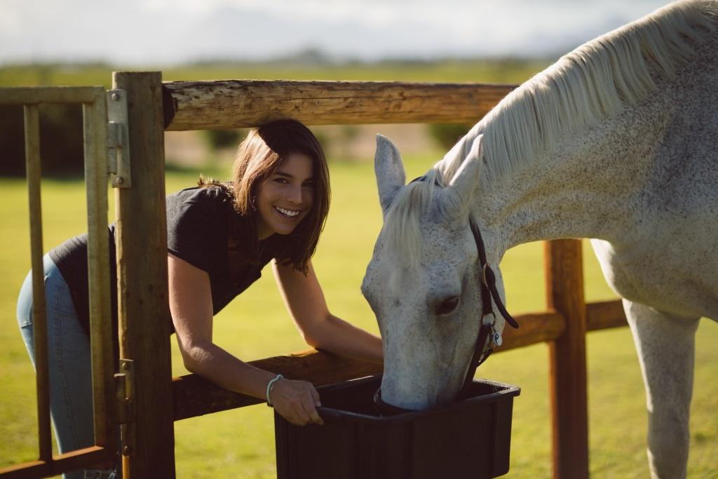 Frau füttert Pferd